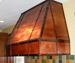 Beautiful copper range hood with clavos and rivets